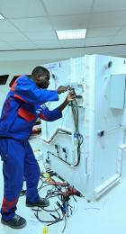 L'apprenti médaillé d'or des épreuves régionales World Skills 2020 Métier Installation Electrique visse un composant sur sa maquette.