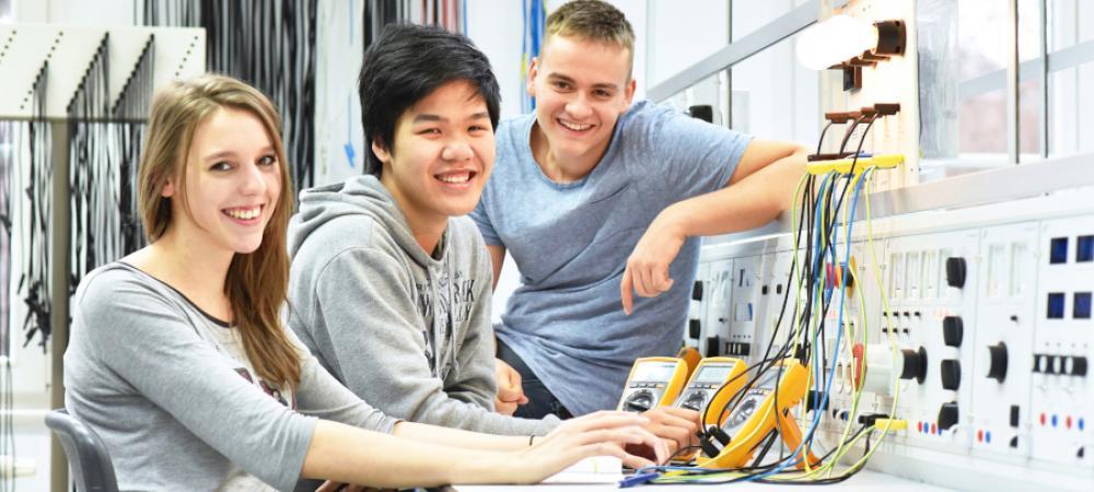 Trois jeunes apprentis en électricité posent tout sourire devant l'objectif, ils sont face à une maquette de tableau et d'ampoules reliés à un multimètre.